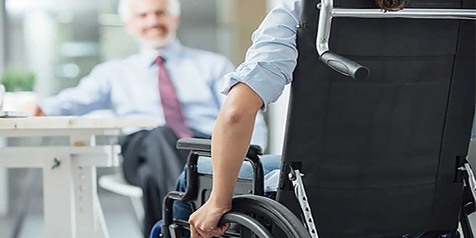 Person in wheelchair facing smiling business man.