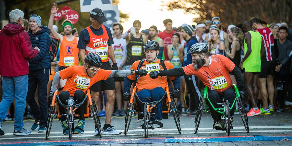 Three men in wheelchairs line up at the start of a race.